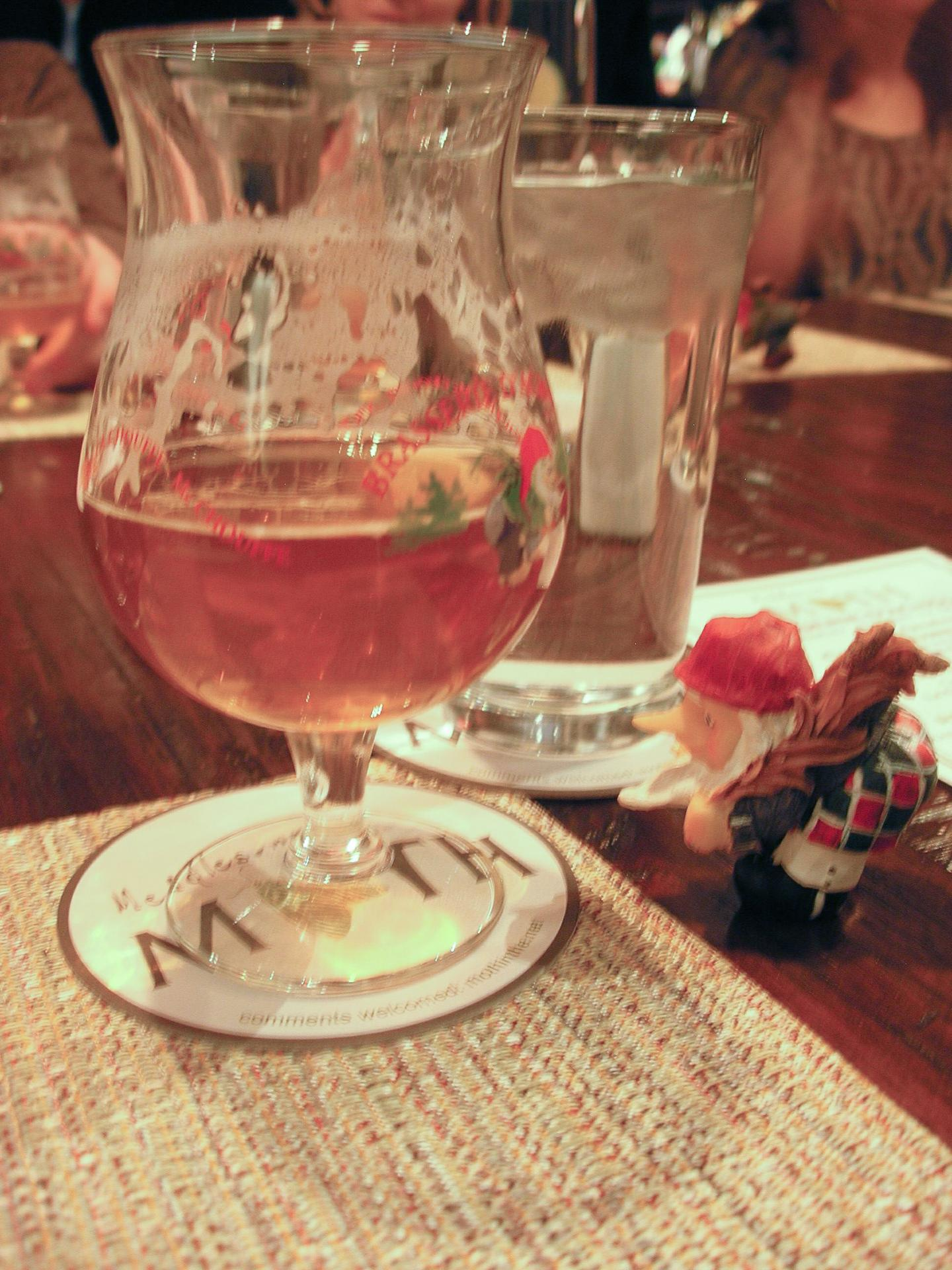 A tiny LaChouffe troll checks out a glass of Houblon Chouffe